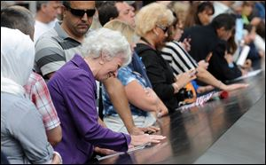A woman weeps over a name inscribed on the edge of the north pool at the National September 11 Memorial in New York City. The memorial was opened Sunday only for relatives of the terrorist attack victims.