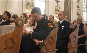 Anthony Santiago, a member of Toledo Fire and Rescue, holds his daughter Kathryn while the names of the fallen are read during the firefighters' Mass at St. Patrick's.