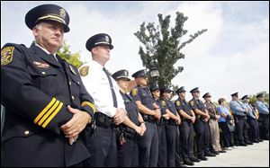 Police Chief William Rhodus, left, joins firefighters and other police officers for the remembrance ceremony at River Centre Park in Sylvania. Sunday's event paid tribute to those who lost their lives in the terrorist attacks and in the armed forces since.