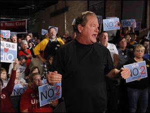 Union supporters hold anti-SB 5 signs behind host Ed Schultz as he talks to the camera.