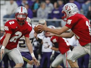 Bowling Green quarterback Andrew Dennis flips the ball to Quinn Donaldson in a game against Maumee.