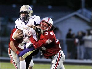Maumee quarterback Jake Schneider is drug down by Bowling Green's Sawyer Shull.