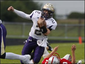 Maumee quarterback Jake Schneider rans from the reach of Bowling Green's Quinn Donaldson.