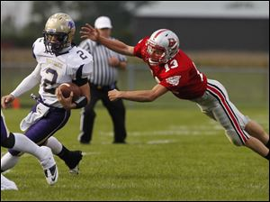 Maumee quarterback Jake Schneider runs from the reach of Bowling Green's Quinn Donaldson.