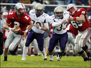 Bowling Green quarterback Andrew Dennis is chased by Maumee's Nick Grzegorzewski (79) and Andrew Schultz.