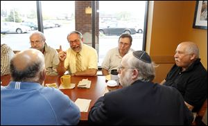Rabbi Moshe Saks, his finger raised, tells a story to members of the coffee klatch, with Sanford Stein at his left, Leon Williams at his right, and Howard Rosenbaum at the table's end.
