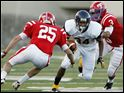 Whitmer running back Jody Webb (34) runs the ball against St. Francis defenders Angelo Spinazze (25) and Shannen Wesley (3) Saturday at the Glass Bowl in Toledo, Ohio.