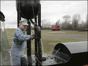 Engineer Brad Taylor, of McComb, O., adds water to the quarter scale steam train on the grounds of the Northwest Ohio Railroad Preservation, Inc. during the Flag City Train Show on Sunday afternoon. Summary: Northwest Ohio Railroad Preservation Inc. 11600 County Rd. 99, Findlay, O.,  reopens for the season with the Flag City Train Show - quarter-size train rides and other festivities.