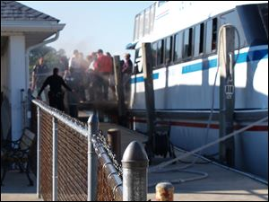 Smoke comes from below the gangplank on the Jet Express as passengers, crew members disembark in Put-In-Bay under the watchful eyes of police and fire officials Saturday.