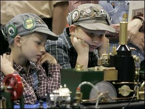 Robert Taylor 7,  left, and Nicholas Taylor, 9, came dressed in train engineer attire to visit the North American Model Engineering Exhibition.  Dad and mom, Brad and Bonnie Taylor, also were similarly attired.  Brad says they love all things related to mechanical engineering, but are especially interested in steam engines, which is what they are watching. They are from McComb, O.  Summary: 17th annual North American Model Engineering Exhibition, put on by the North American Model Engineering Society, at the SeaGate Centre in Toledo.