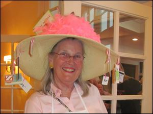 Kay Foster sells raffle tickets while sporting a special hat made for the occasion with tags bearing the description of the prizes.