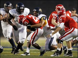 Whitmer's Chris Wormley (47) stops St. Francis' Jarrod Jefferson (20) at the Glass Bowl.