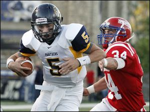 Whitmer quarterback Tyler Palka (5) scores a touchdown against St. Francis defender Scott Wawrzyniak (34)  at the Glass Bowl.