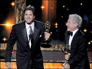 Steven Levitan, left, and Jeffrey Richman  accept the award for outstanding writing for a comedy series for