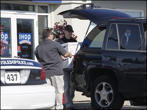 Law enforcement load boxes taken from the Airport IHOP into the trunk of a black SUV.