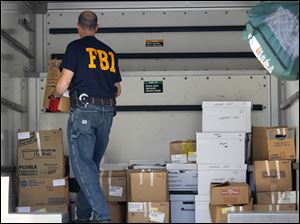 An FBI agent loads boxes from the Airport Highway IHOP into a moving van.
