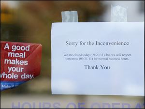 A sign on the door of the Airport Highway IHOP says the business is closed Tuesday morning.