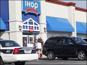 Authorities take boxes out of an IHOP Restaurant on Talmadge Road as part of a raid affecting several area locations.