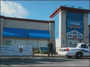 A police officer guards a stack of boxes removed from the IHOP Restaurant on Fremont Pike in Wood County.