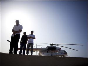 Helicopter pilots perform prayers at a field hospital near Sirte, Tuesday, Sept. 20, 2011. Revolutionary fighters have not been able to take over central positions in Sirte. Pro-Gadhafi forces have the advantage of knowing the city and are heavily armed, making it impossible for the former rebels to stand in at night after advancing during the day.