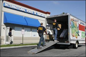 Law enforcement officials remove boxes from the IHOP restaurant on Airport Highway in Holland on Tuesday morning.