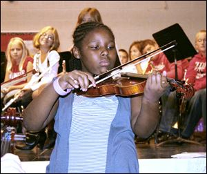 DeKayla Adams, a violin player from Waterloo Elementary School, shows the student body how to play a popular fiddle tune.