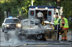 In this Tuesday, Sept. 20, 2011 photo, a Monroe firefighter sprays water on a burning car on Elm Street in Monroe, Mich.