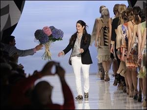 Italian designer Veronica Etro receives a bouquet of flowers at the end of the presentation of her Spring-Summer 2012 fashion collection in Milan, Italy.