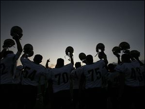 St. John's players raise their helmets to the sky before playing Whitmer Sept. 23, 2011.