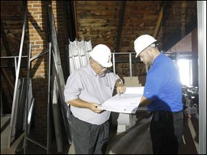 Joseph Lenhart, left, and Jason Fleming, right, look at the blueprints in the Auglaize County  courthouse.