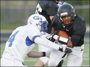 Anthony Wayne's Brian Butts (4) defends against Perrysburg ball carrier Tyler Gordon (12) .