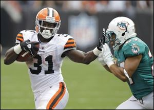 Browns running back Montario Hardesty (31) stiff arms Dolphins cornerback Jimmy Wilson after a pass reception in the fourth quarter Sunday in Cleveland.