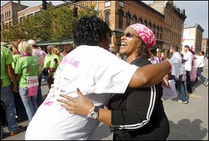 Stephanie Lincoln, left, hugs her friend Yolanda Willis as she runs by during the Komen Northwest Ohio Race for the Cure in downtown Toledo. The head scarf was in keeping with the color of the day.