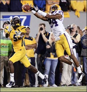 LSU's Tharold Simon, right, breaks up a pass to West Virginia's Ivan McCartney Saturday in Morgantown, W.Va.