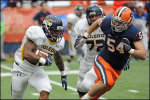 Toldeo running back David Fuellen (22) is chased by Syracuse's Mikhail Marinovich (54) during Saturday's game in Syracuse, N.Y.