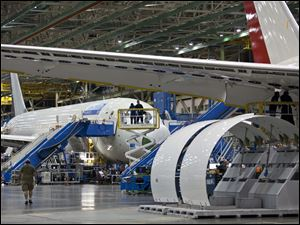News media groups tour the assembly line of the Boeing Co. 787 in Everett, Wash., Sunday.