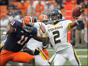 Toledo quarterback Terrance Owens (2) throws a pass a Syracuse's  Marquis Spruil, left, rushes in during Saturday's game at Syracuse. The final was 33-30 in favor of Syracuse.