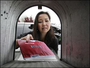 Carleen Ho poses with a Netflix movie she is picking up from her mail box in Palo Alto, Calif.