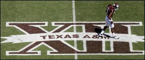 In this photo taken Saturday Texas A&M wide receiver Nate Askew (9) walks across a Big 12 logo on Kyle Field.