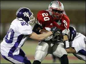 Central's Edwards (20) is stopped by Fremont Ross defenders Michael Egbert (20) and Jordan Garcia (23).