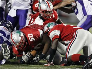 Central Catholic's Jon Perrin (50) attempts to recover Fremont Ross running back Jabree Lather's fumble.
