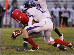 Bedford's Jonathan Shepherd (39) attempts to recover his fumble while tackled by Ann Arbor player Tommy Pokorney, 13.