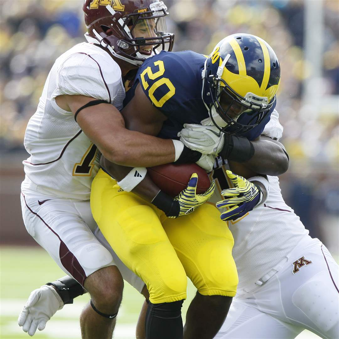 Michigan-s-Michael-Shaw-is-tackled-by-the-Gophers-defense