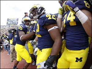 Players Kevin Koger (86) Dylan Esterline (42) and Steve Watson (84) prepare to lead the Wolverines onto the field to play the University of Minnesota at Michigan Stadium, Saturday.