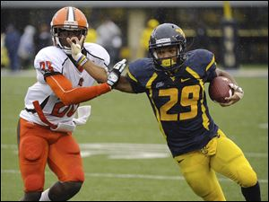 West Virginia's Dustin Garrison pushes away Bowling Green's Aaron Foster during the quarter of an NCAA college football game Saturday, Oct. 1, 2011, in Morgantown, W.Va. (AP Photo/Tyler Evert)