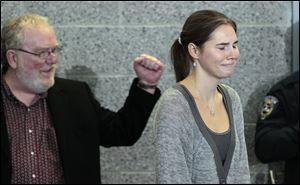 Amanda Knox, right, is cheered by family friend Dave Marriott as she arrives for a news conference shortly after her arrival at Seattle-Tacoma International Airport Tuesday, Oct. 4, 2011