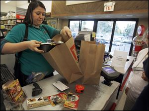 Cashier Denise Cruz checks out customers' purchases at a hardware store in Los Angeles Tuesday, Oct. 4, 2011.   Service firms that employ 90 percent of the U.S. work force grew at a slower pace in September, evidence that the economy is growing but at a sluggish pace.