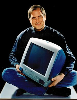 This 1998 file photo provided by Apple shows Apple CEO Steve Jobs holding an iMac computer.
