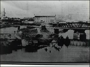At Lock No.1, later renumbered as No. 52, on the Swan Creek Sidecut, which is today the location of the Collingwood Extension. Erie Street, in the foreground, crosses both Swan Creek and the Canal Side Cut by way of iron bridges between Collingwood and Hamilton Avenue. The building in the center of the photo is the former Detwiler Mill.