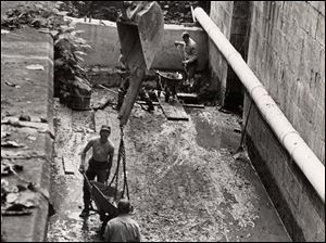 A crew of Metroparks of Toledo Area maintenance men, rangers and CETA workers haul away the last of more than 100 cubic yards of silt from the bottom of the old Miami & Erie Canal Lock at Side Cut Metropark in Maumee, Sept. 15, 1983. The backhoe was used to lift filed wheelbarrows from the lock and lower empties.